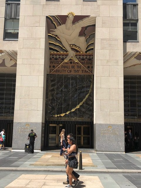 This is a closeup of the entrance to Rockefeller Center. Over the door is a sculpture of Greek god maybe, with this inscription: Wisdom and knowledge shall be the stability of thy times.