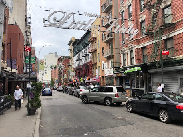 "Photo of a street with ""Welcome to Little Italy"" sign going across it"