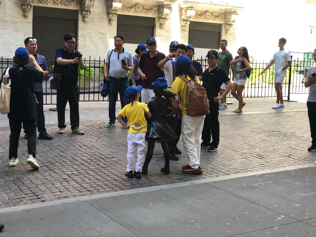 An Asian family interacting with a statue of a little girl in front of NYSE