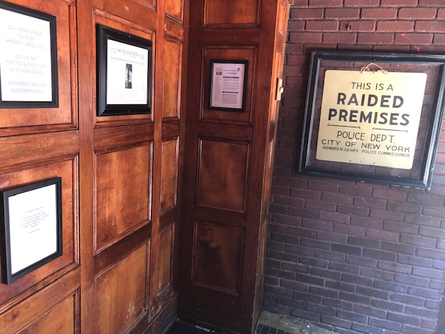 """Frames sign on the right: """"This is a Raided Premises""""; frame newspaper articles on the left"""
