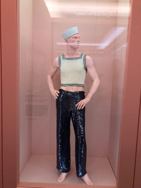 Male mannequin in a title tank top with his belly button showing, navy hat, and black lame pants.