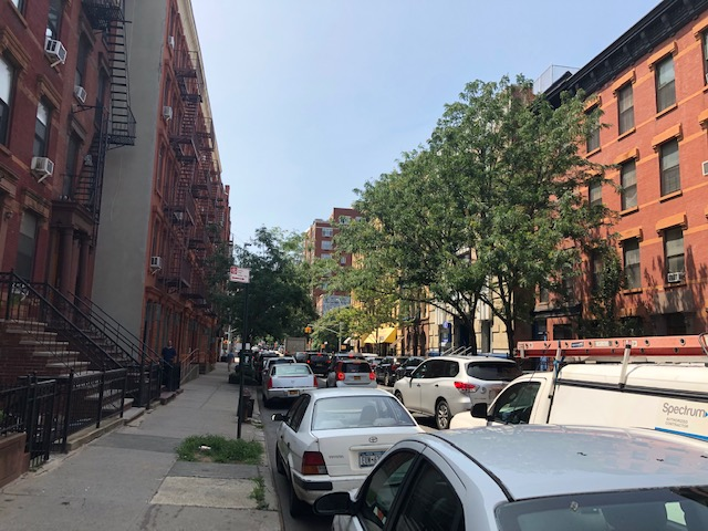 residential street with typical NYC buildings with fire escapes