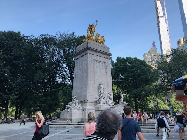 Huge pillar at the entrance to Central Park, with a gold sculpture at the top of it, and stone sculptures at street level in front