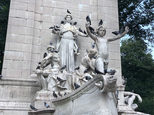 Closeup of statue at Central Park, of about 5 people, 3 of which have outstretched hands
