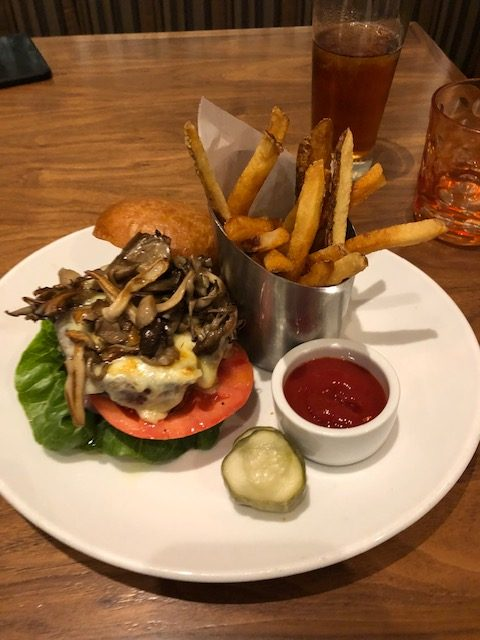 Hamburger sitting on bun, lettuce, tomato, smothered in cheese and mushrooms, fries standing up in a stainless steel container