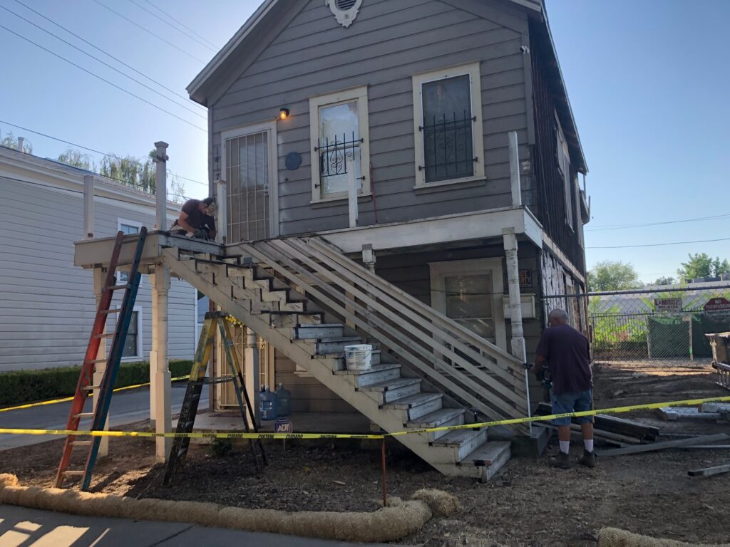 Porch fence gone, workers starting to work on the stairs