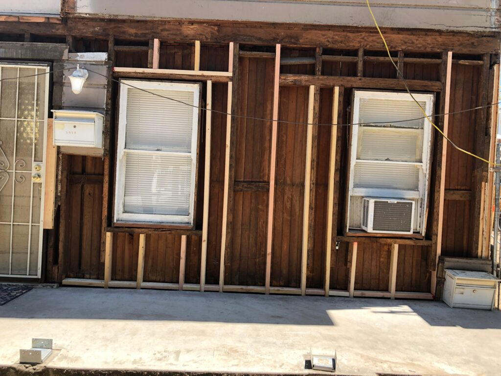 front of house, siding removed, with fresh wood in places