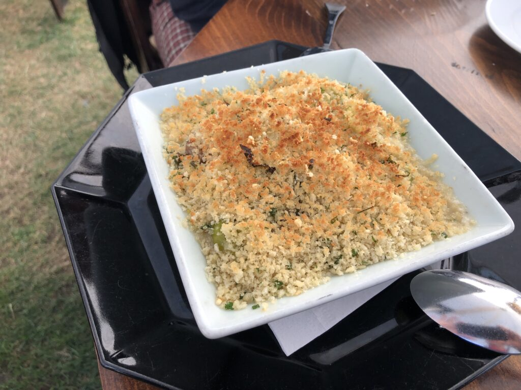 square white dish where really all you can see if a layer of browned plank crumbs on top of something greenish