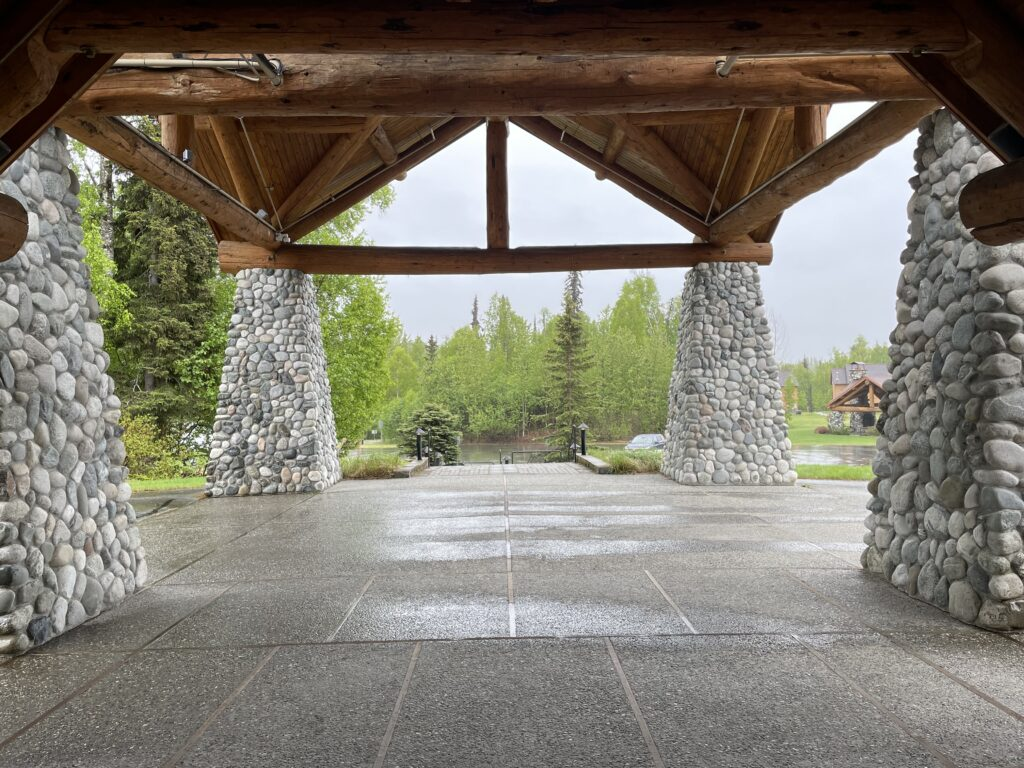 Under that same entrance, with 4 stone pillars holding up a massive log ceiling.