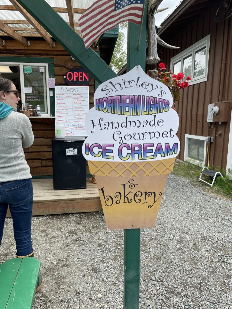 "Sign looks like an ice cream cone: ""Shirley's Northern Lights Handmade Gourmet Ice Cream"" on the ice cream part, ""& bakery"" on the cone."
